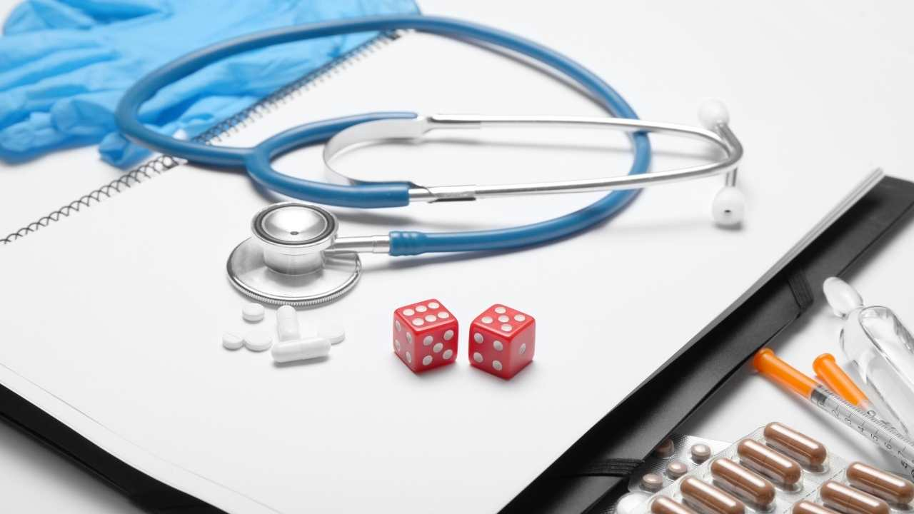stethoscope, medication, and dice on a notebook