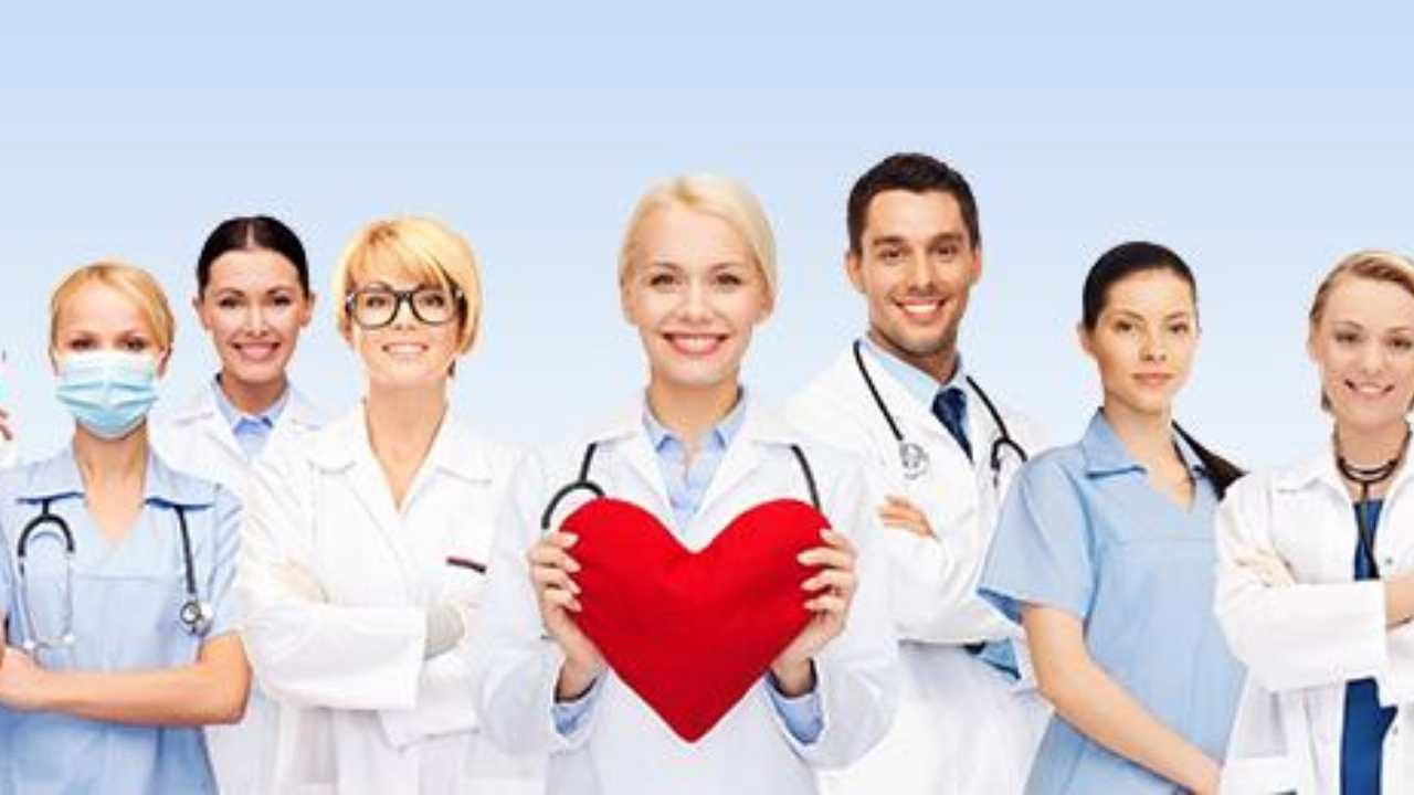 row of doctors and nurses posing, center doctor with a red fabric heart